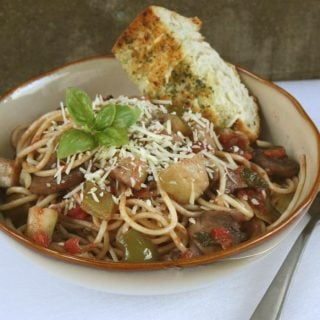 Pasta and roasted vegetables in a brown bowl with garlic bread