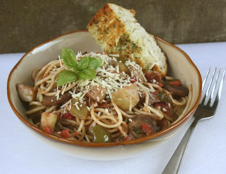 Roasted Vegetable Pasta in a brown bowl with garlic bread