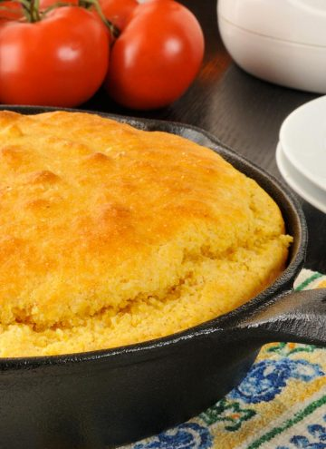 The best cornbread in a cast iron skillet with tomatoes in the background
