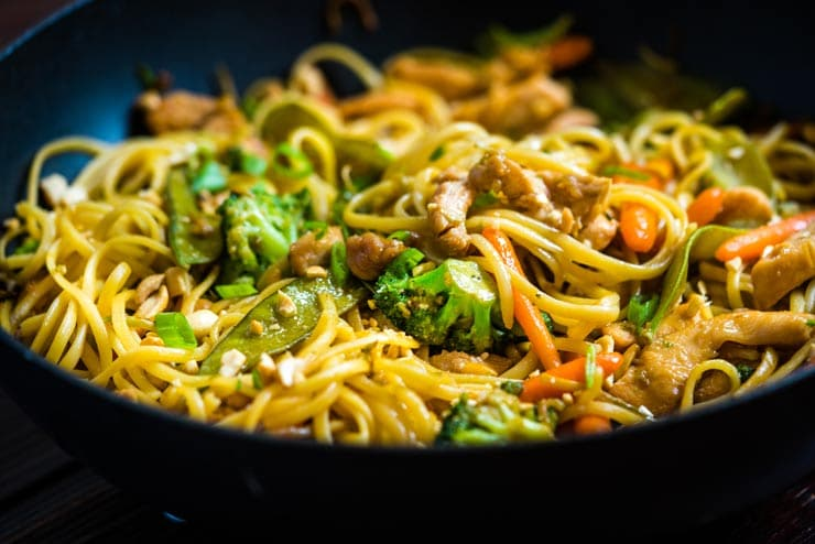 Chicken Lo Mein Recipe in wok with broccoli, carrots and peas
