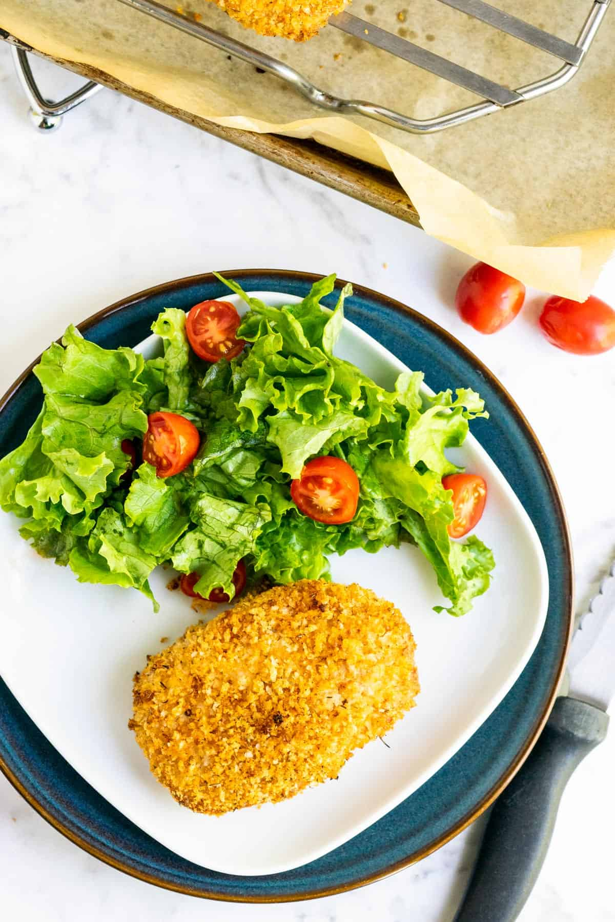 Overhead shot of breaded pork chop on a white plate with a salad