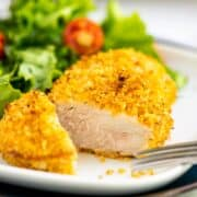 Breaded pork chop sliced on a white plate with a green salad and forl