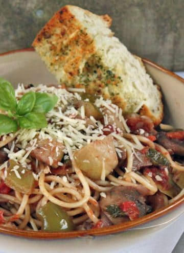 Pasta with roasted vegetables in a brown and white bowl with garlic bread