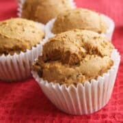 pumpkin muffins in white wrappers on a red cloth