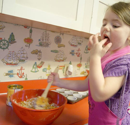 young girl licking her fingers while stirring muffin batter
