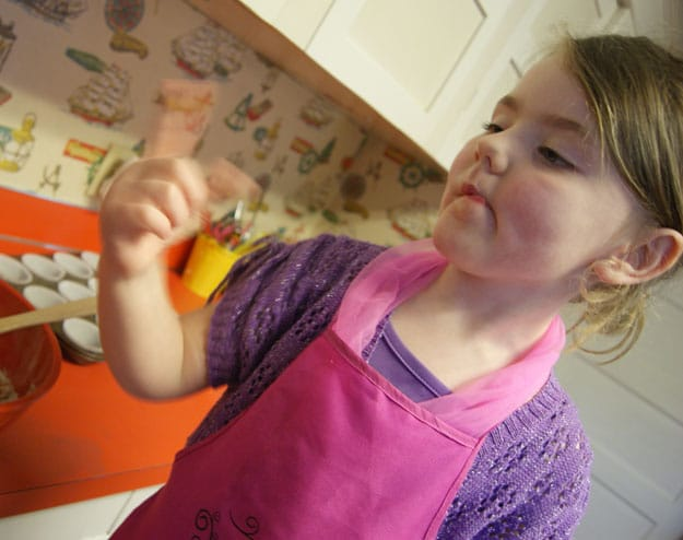 young girl licking fingers in a pink apron