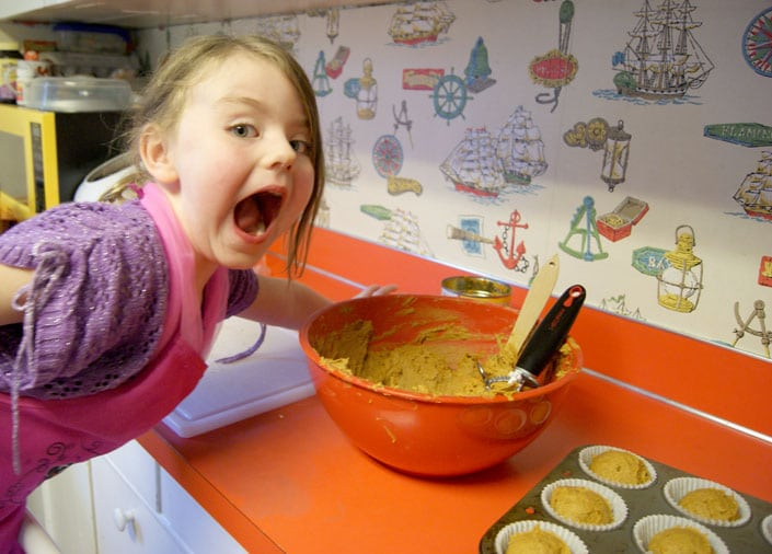 young girl excited about muffin batter in a red bowl