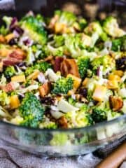Glass bowl full of sweet broccoli salad with bacon, currants, onion, cheese and sunflower seeds