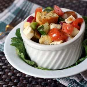 Panzanella Salad in white bowl on top of a lettuce leaf in another white bowl on a placemat with a fork