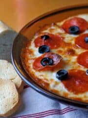 Baked Pizza Dip in pie dish with a white and red towel and toasted bread slices