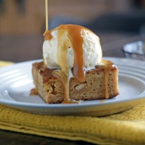 Caramel blondie brownie with a scoop of ice cream and caramel drizzled on top on a white plate