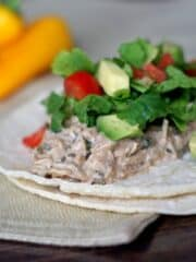2 corn tortillas with chicken, lettuce, tomato and avocado on a tabletop