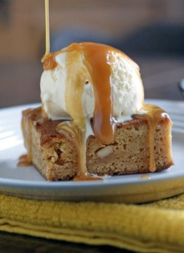 Caramel Cashew Blondies on a white plate with a scoop of ice cream on top and caramel sauce being drizzled on top