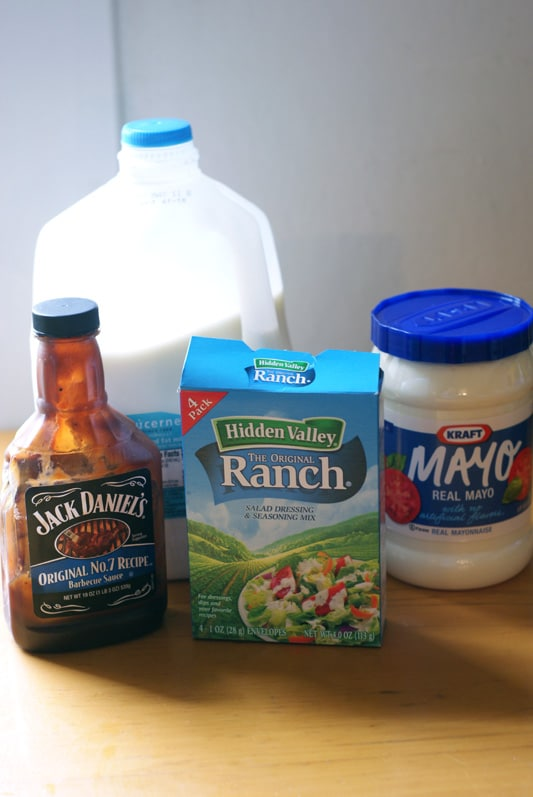 Milk, ranch, BBQ and Mayo on a wooden table.