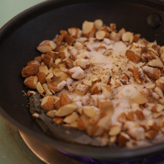 cut up almonds in a pan with sugar