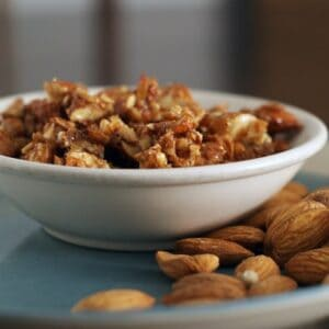 honey almonds in a white bowl on blue plate