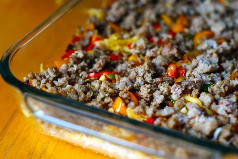 shredded potatoes, cheese, bell peppers and sausage in a glass dish