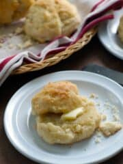 split biscuit with butter on top on a white plate