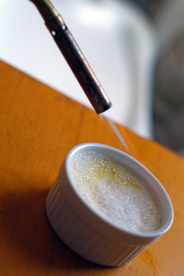 close up of torch melting sugar