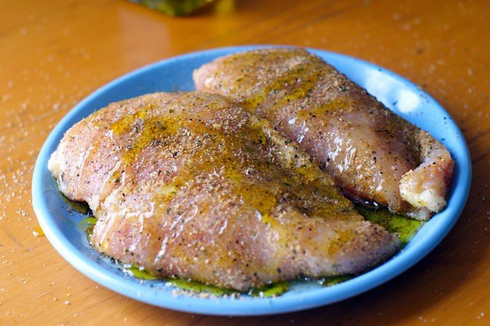 two seasoned chicken breasts on a blue plate
