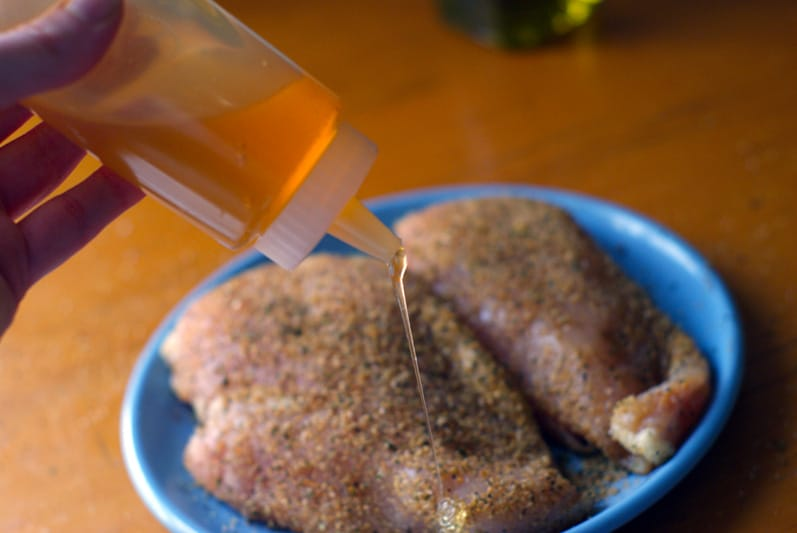 drizzling honey on seasoned chicken breasts