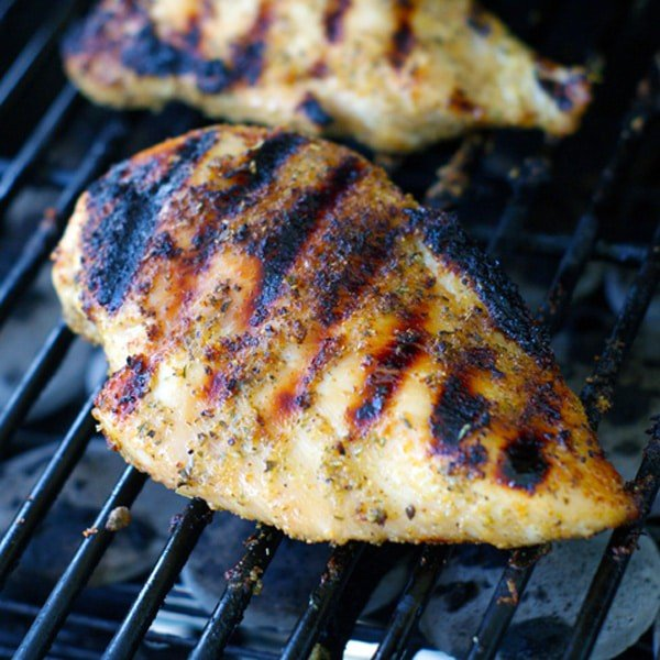 Seasoned chicken breast on grill