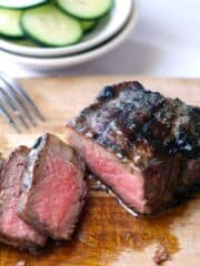 grilled steak sliced on a wooden cutting board