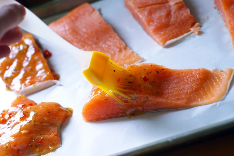 brushing raw salmon fillets with the chili sauce