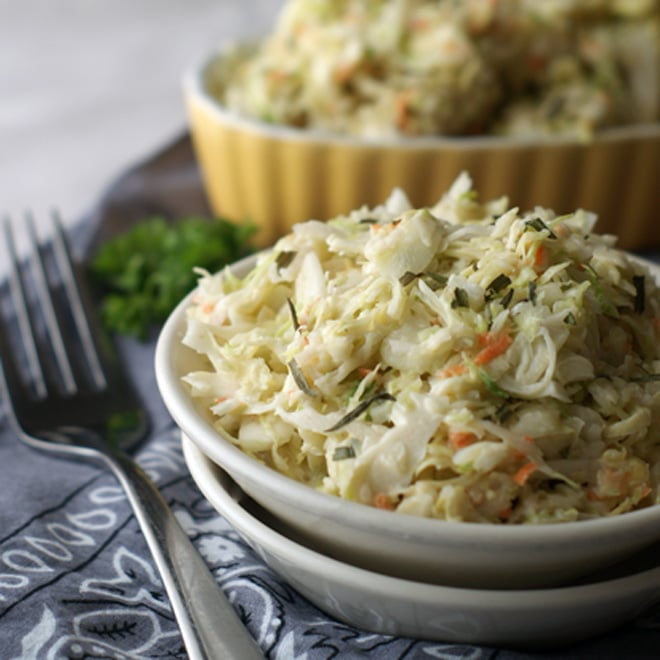 Cabbage coleslaw in white bowl on grey napkin and fork