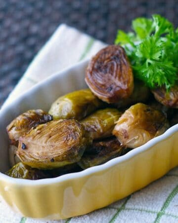 roasted brussels sprouts in a yellow dish with parsley