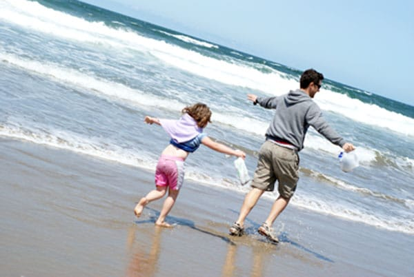 dad and daughter running on the beach