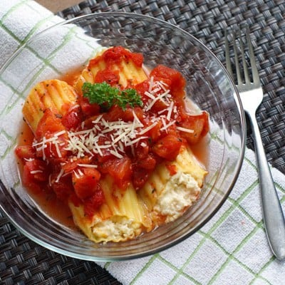 Cheese stuffed manicotti in a glass bowl on a white and green towel