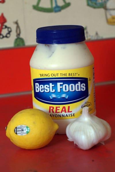 jar of mayonnaise, lemon, and garlic on an orange counter