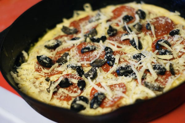 unbaked pizza topped with cheese, pepperoni and olives