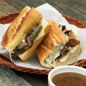 French dip sandwiches on a wicker plate with a bowl of au jus