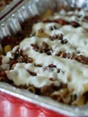 bechamel sauce drizzled over pasta al forno in foil pans
