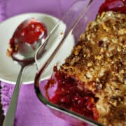 Cherry dump cake in a glass baking dish on a pink napkin