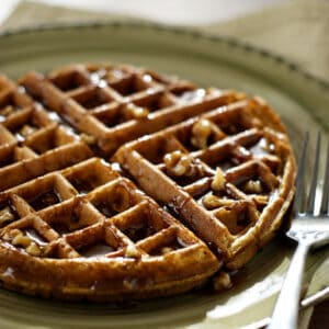 Pumpkin Waffles w/ Praline Pecan Syrup on a green plate
