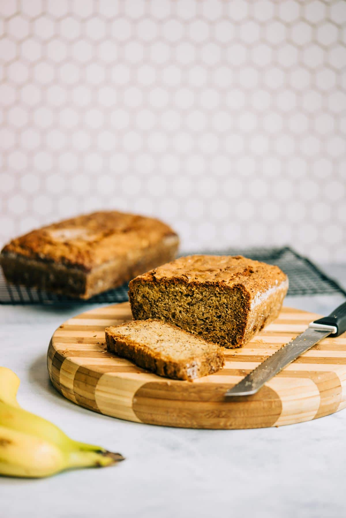 A loaf of sliced banana bread on a striped cutting board with knife