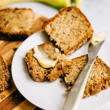 Sliced banana walnut bread on a white plate with butter