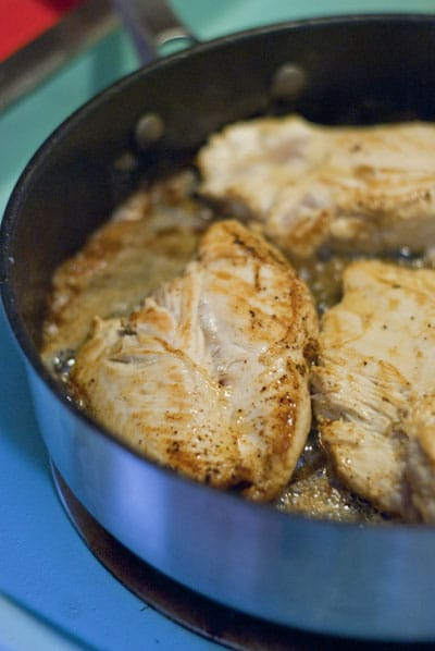 chicken breasts browning in a pan