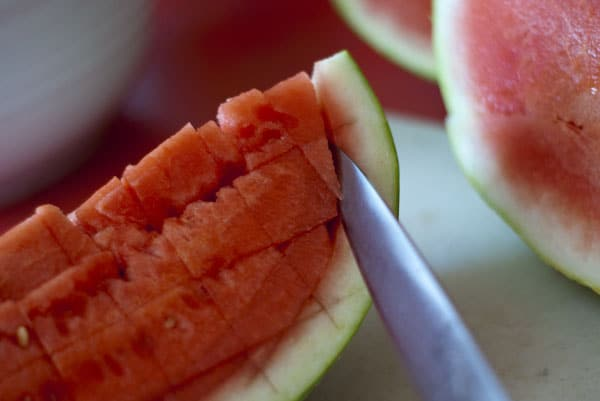 Using a knife to cut into a watermelon and making diced watermelon.