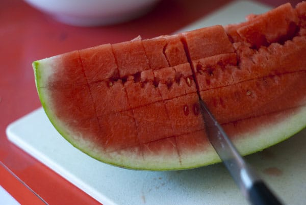 Making vertical lines on a watermelon with a knife.