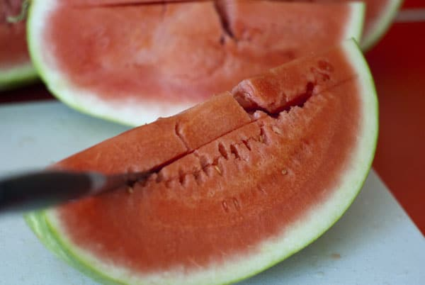 Cutting into a slice of watermelon on a white cutting board.