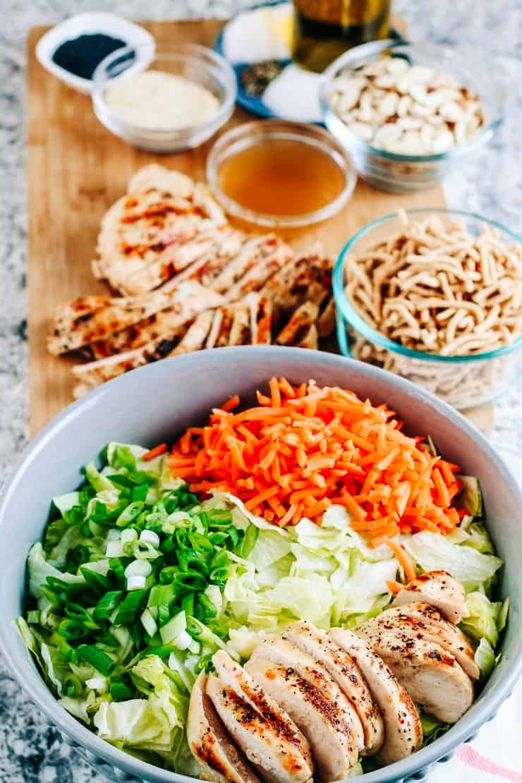 Chinese chicken salad with carrots, green onions and lettuce on a cutting board with dressing, crunchy noodles, almonds and sesame seeds.