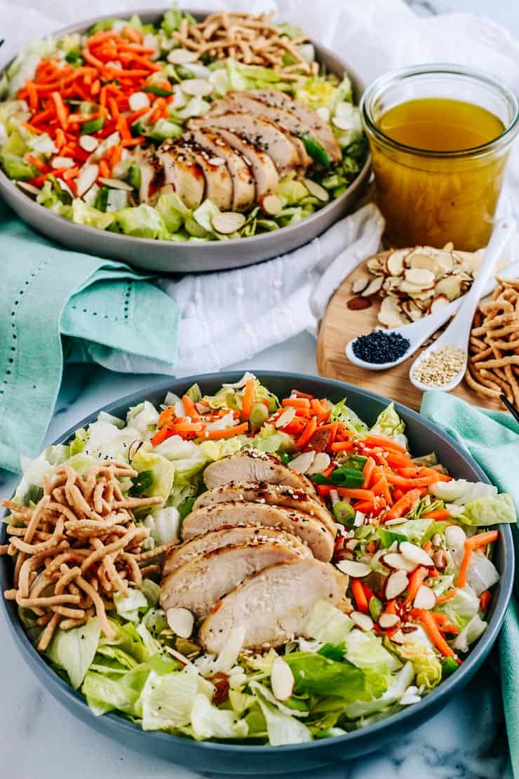 Two Asian salads with grilled chicken in a grey bowls on a white tablecloth with dressing, almonds, and sesame seed next to them.
