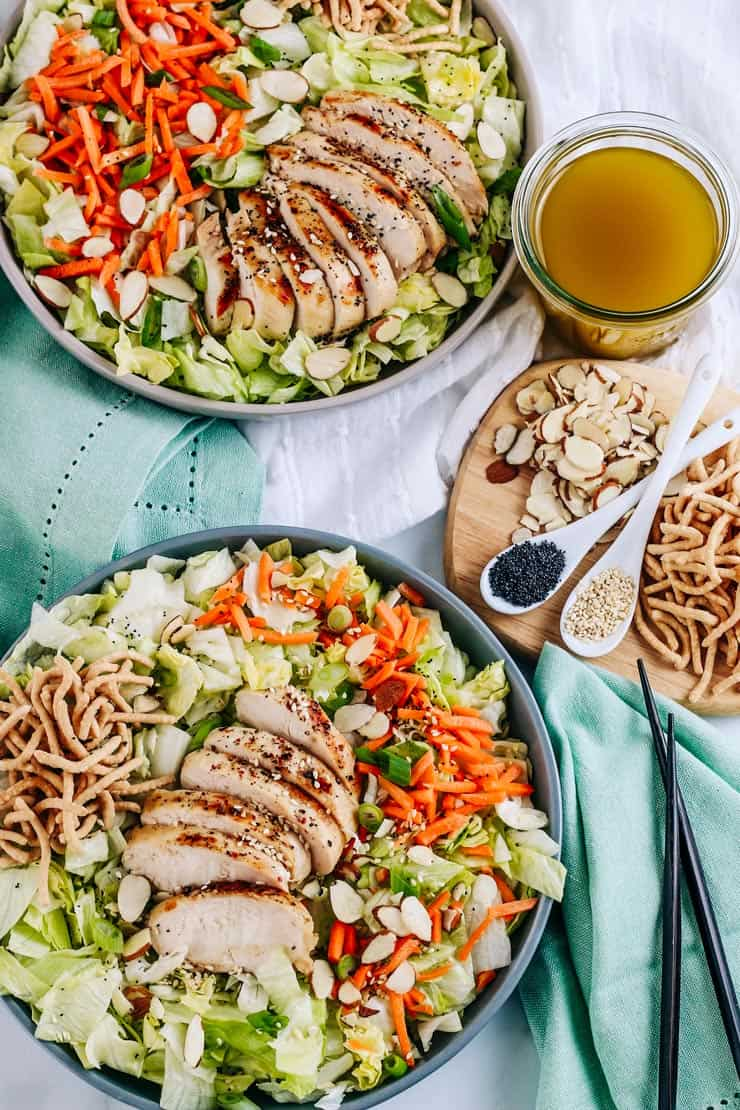 2 bowls of salad in grey bowls with a glass of asian salad dressing, almonds, poppy seeds, and crunchy noodles next to them.