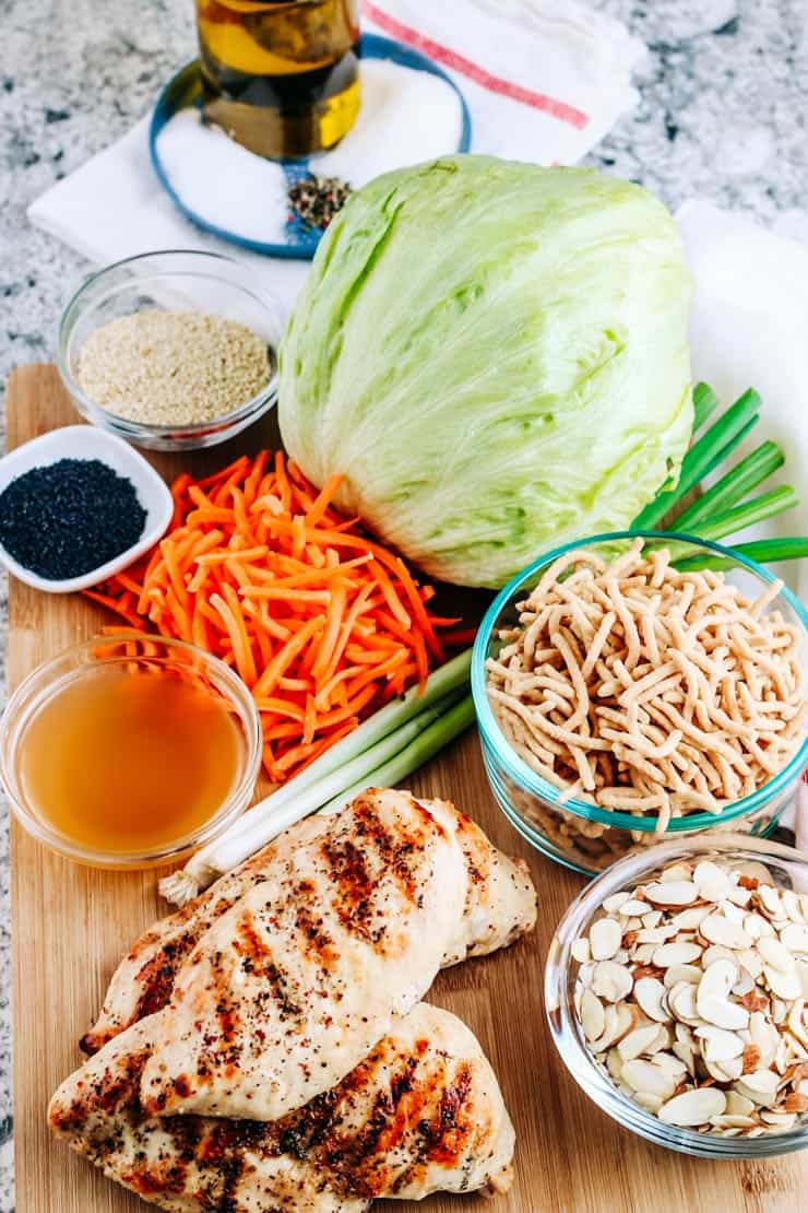 Grilled chicken, cabbage, carrots, noodles, almonds and poppy seeds on cutting board