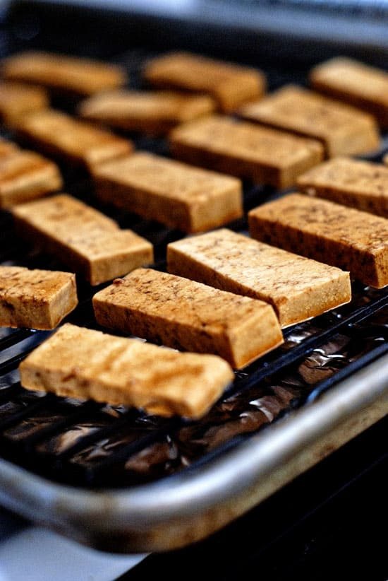 Tofu cut into rectangles spread out on a baking sheet.