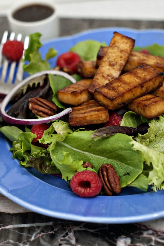 Simple raspberry and balsamic salad with fresh onions, spinach and raspberries on a large blue serving plate.